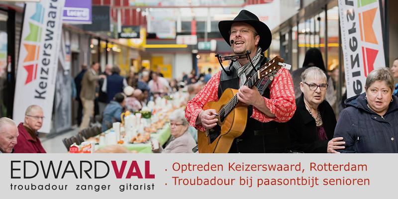 Troubadour zanger gitarist Edward Val | Optreden Paasontbijt senioren ouderen | Winkelcentrum Keizerswaard Rotterdam Zuid Holland | Improvisatieliedjes | Fotograaf Hans Tak | Muzikaal interactief entertainment